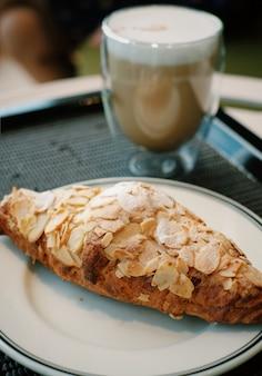 Closeup croissant aux amandes avec fond de café chaud