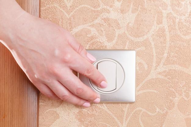 Closeup doigt appuyer allumer / éteindre l'interrupteur électrique
