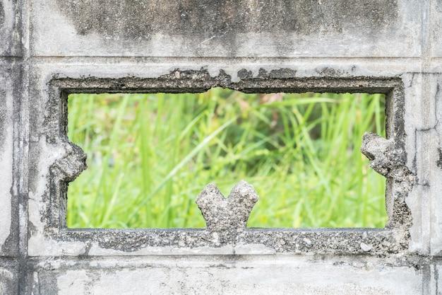 Closeup endommagé mur de ciment sale avec fond flou d'herbe verte