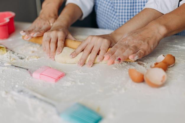 Closeup femelle mains fille et mère sont remuer la pâte.