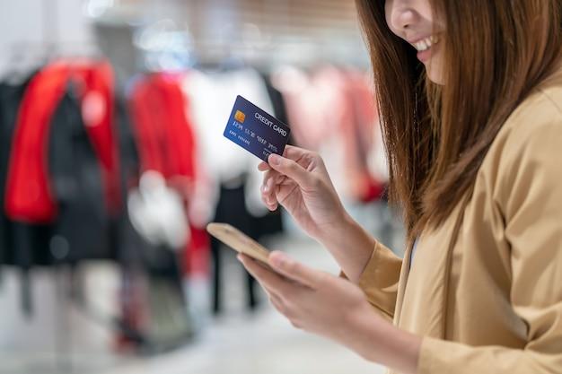 Closeup femme asiatique à l'aide de carte de crédit avec téléphone portable pour les achats en ligne dans les grands magasins