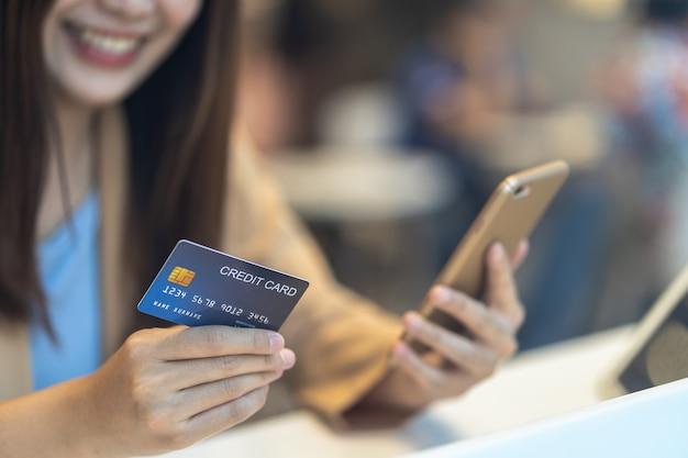 Closeup femme asiatique à l'aide de carte de crédit avec téléphone portable pour les achats en ligne dans le magasin