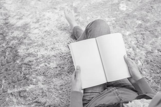 Closeup, femme asiatique, séance, sur, gris, tapis, à, plancher, dans, les, maison, fond texturé, pour, lire livre, dans, temps relâche