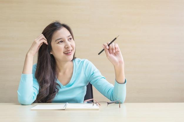 Closeup femme asiatique travaillant avec un visage heureux et un stylo à la main sur un bureau en bois flou