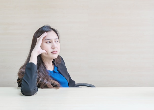 Closeup femme asiatique travaillant avec le visage pensant dans la salle de réunion