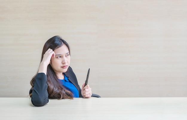 Closeup femme asiatique travaillant avec le visage pensant