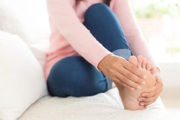 Closeup femme assise sur le canapé tient sa blessure au pied, ressentant une douleur.