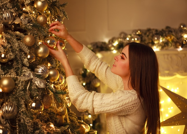 Closeup, femme, décorer, arbre noël, nouvel an, jouets, chez soi
