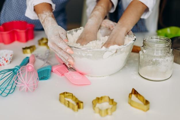 Closeup femme et enfants mains dans une assiette pétrir la pâte