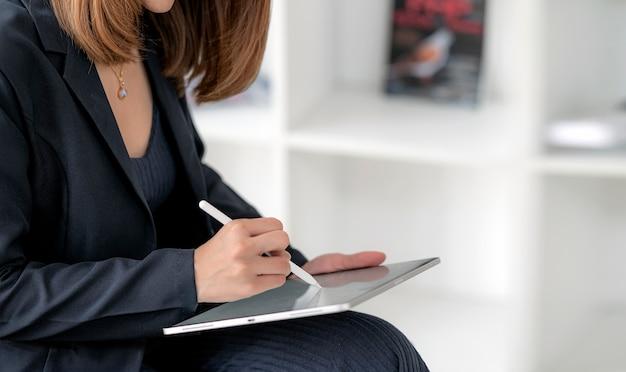 Closeup femme main écrit sur l'écran de la tablette avec un stylo numérique.