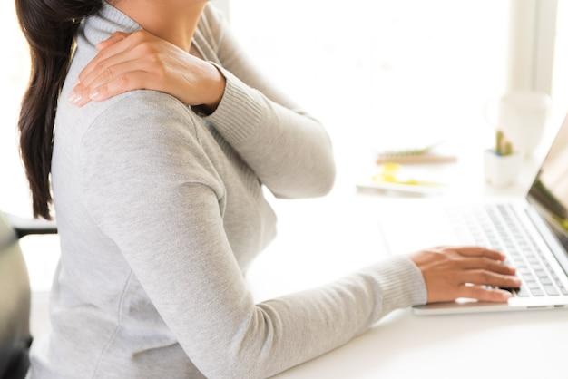 Closeup femme avec les mains tenant sa douleur à l'épaule. syndrome de bureau