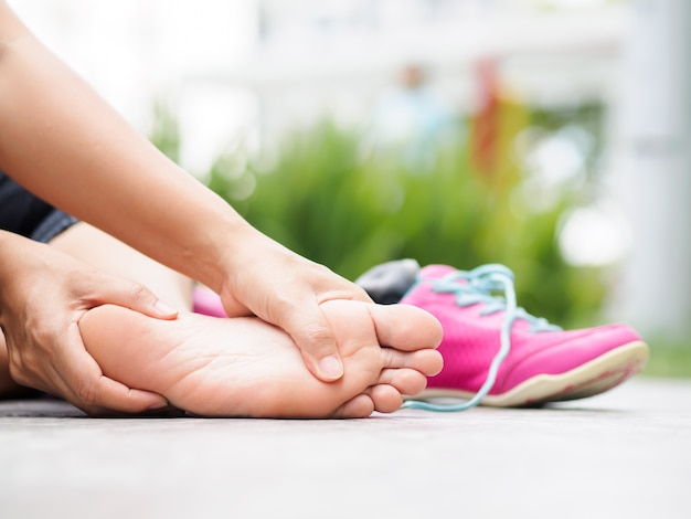 Closeup femme masser son pied douloureux pendant l'exercice