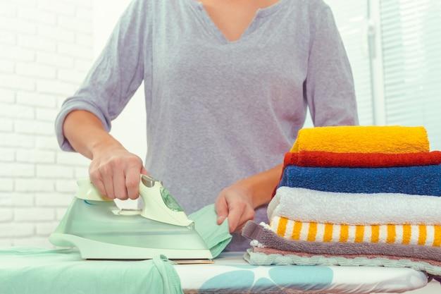 Closeup, femme, repasser, vêtements, planche repasser