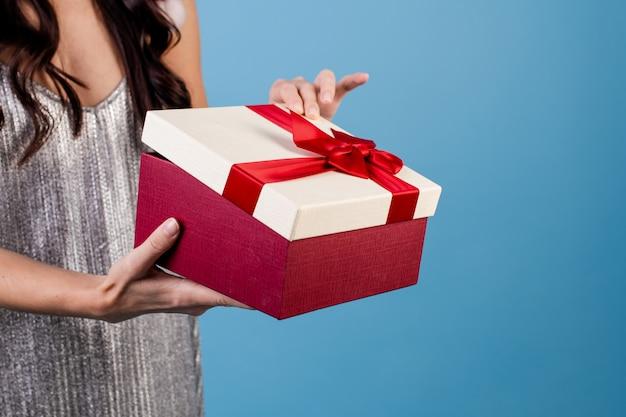 Closeup femme tenant une boîte cadeau avec ruban rouge isolé sur bleu