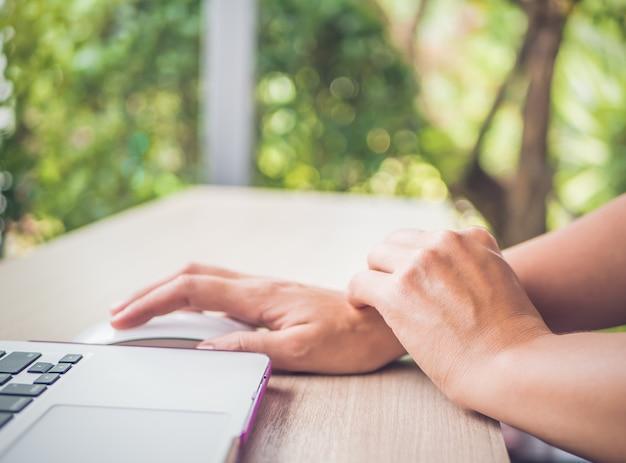 Closeup femme tenant sa main douloureuse d'utiliser l'ordinateur.