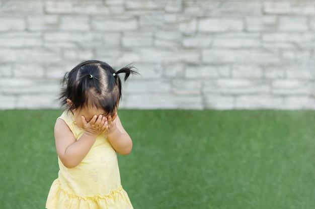 Closeup fille asiatique enlève ses mains sur le visage et joue caché avec quelqu'un sur le sol d'herbe