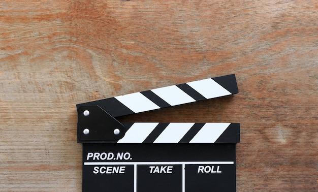 Closeup film clapper board sur table en bois avec flou artistique et plus de lumière en arrière-plan