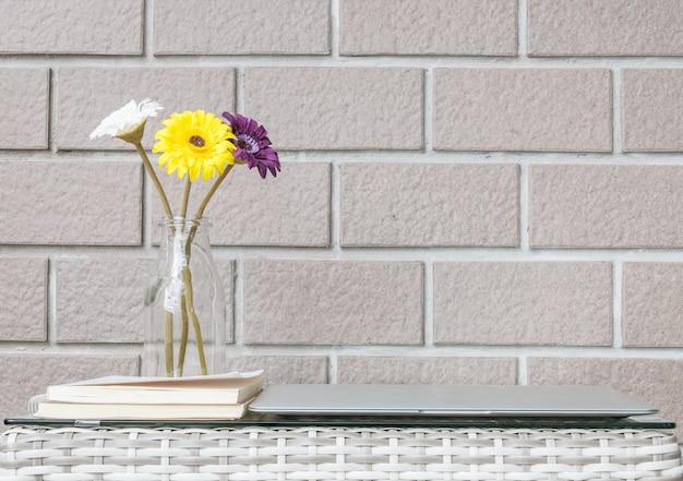 Closeup fleur artificielle sur table en bois tissé