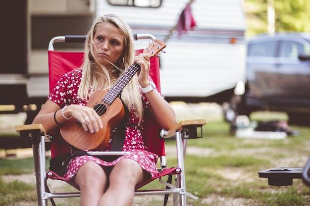 Closeup focus portrait d'une belle jeune femme tenant un ukulélé