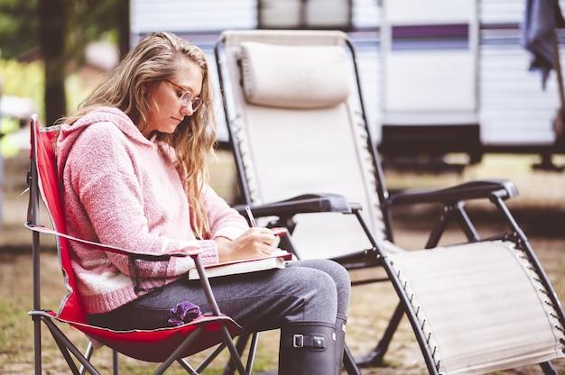 Closeup focus portrait d'une jeune femme écrivant dans son journal