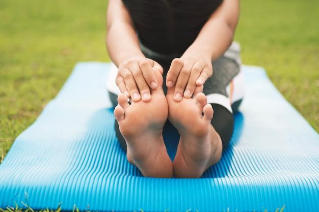 Closeup foots d'une jeune femme pratiquant l'yoga au parc
