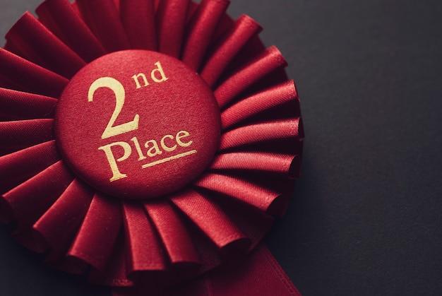 Closeup gagnant 2ème place rosace rouge avec texte or sur fond noir