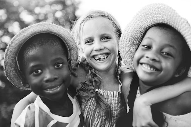 Closeup groupe de divers enfants souriants en niveaux de gris