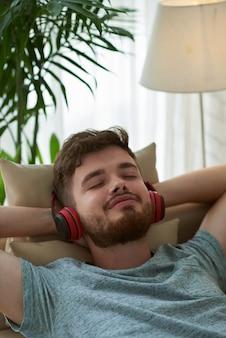 Closeup, homme, apprécier, musique, coucher divan, mains, derrière, tête
