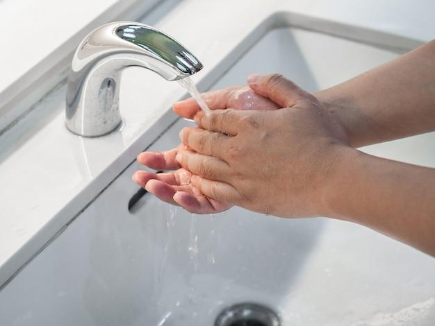 Closeup homme se laver les mains sous le robinet avec de l'eau dans la salle de bain.