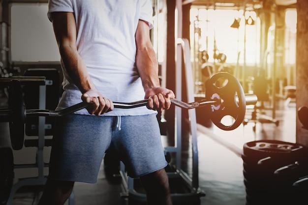 Closeup hommes en bonne santé tenant entraînement haltère et bâtiment du corps au fitness gym