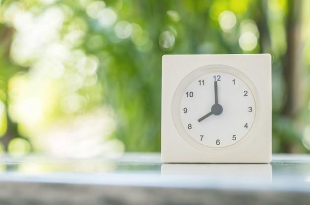 Closeup horloge blanche sur une table de marbre floue dans le fond du jardin