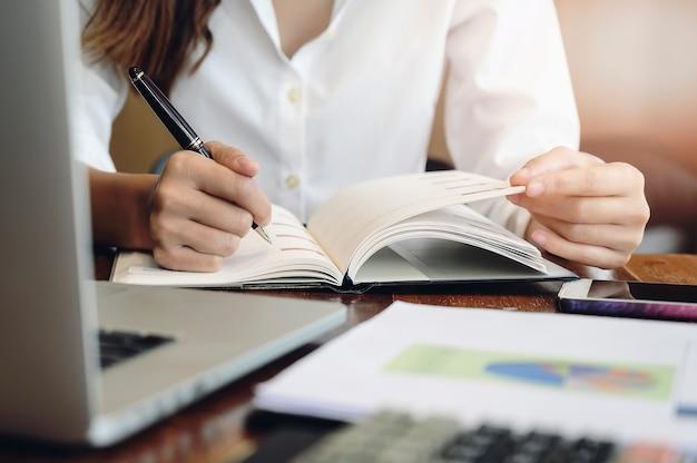 Closeup image main féminine tenant un stylo et écrit sur le journal