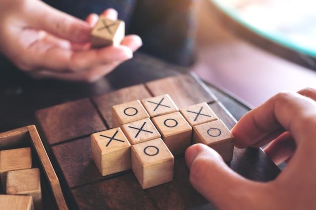 Closeup image de personnes jouant en bois jeu tic tac toe ou ox jeu