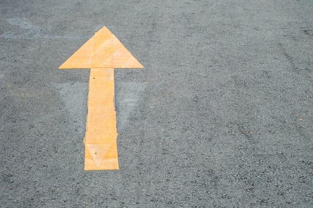Closeup jaune peint flèche signe sur fond de plancher de rue de ciment