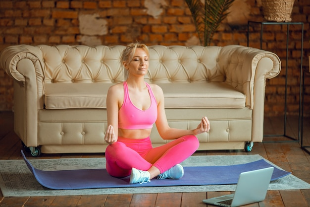 Closeup jeune entraîneur de femme mince en forme sportive pratique la formation en ligne vidéo instructeur de yoga moderne à la caméra méditer se détendre respirer siège facile pose gym concept de mode de vie sain séance d'entraînement à la maison