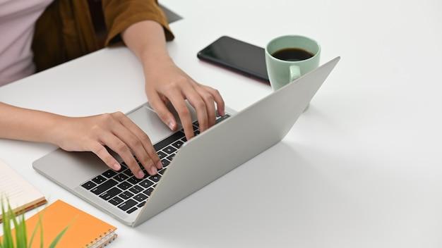 Closeup jeune femme à l'aide d'un ordinateur portable sur l'espace de table et de copie de bureau.