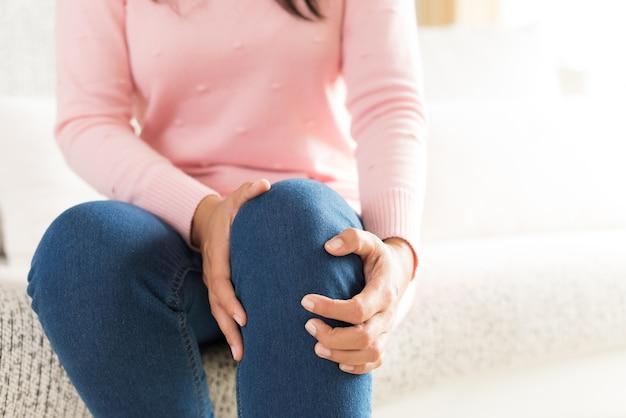 Closeup jeune femme assise sur le canapé et ressentant une douleur au genou