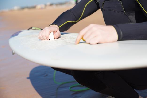 Closeup, jeune, homme, cirer, planche surf, plage ensoleillée