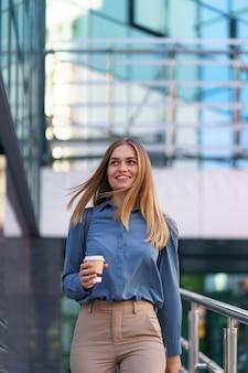 Closeup jolie femme en mouvement avec café à emporter sur le bâtiment de l'entreprise. portrait fille blonde tenant une tasse de papier avec une boisson chaude en plein air.