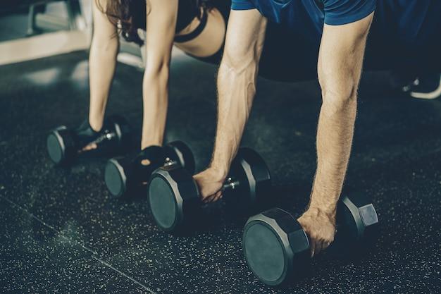 Closeup main couple diversité travaillant dans le complexe de sport de remise en forme de gym, séance d'entraînement travaillant sur les bras et le cardio, position de posture, push up sur les poids, faire une planche sur kettlebell.sports et concept de santé