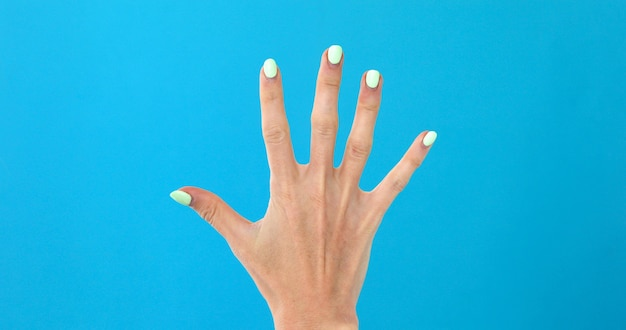 Closeup main féminine comptant jusqu'à 5