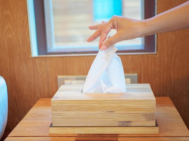 Closeup main féminine cueillette d'un tissu blanc de la boîte à mouchoirs