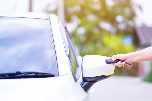 Closeup main de femme tenant les systèmes d'alarme de voiture de contrôle à distance