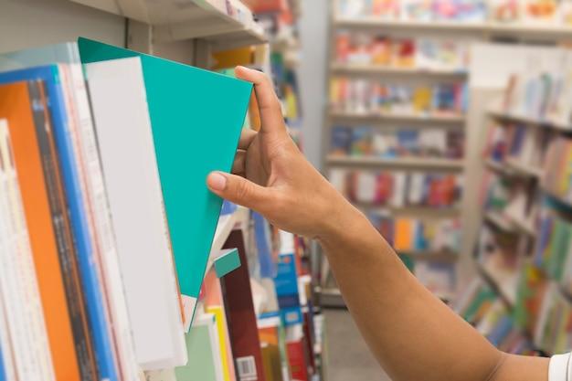Closeup main sélectionnant un livre dans une bibliothèque