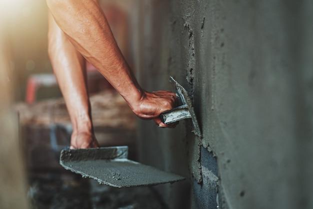 Closeup main de travailleur plâtrant du ciment au mur pour la construction d'une maison