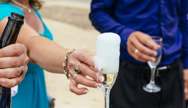 Closeup mains de la mariée et le marié avec des verres de champagne