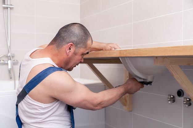 Closeup mâle plombier travailleur en uniforme bleu denim, salopette, fixation évier dans la salle de bain avec mur de carreaux. service professionnel de réparation de plomberie, installation de canalisations d'eau, canalisation d'égout montée sur un homme