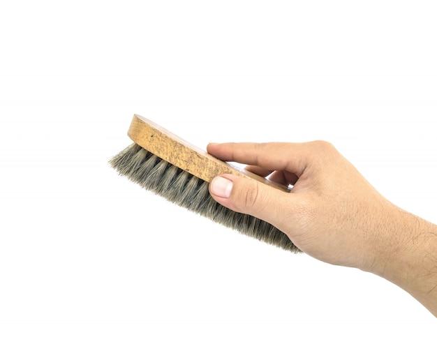 Closeup man main utiliser shoebrush isolé sur blanc avec un tracé de détourage