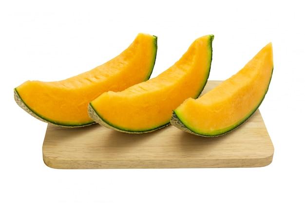Closeup melon couleurs vives qui est des morceaux sur un plateau en bois isolé sur fond blanc.