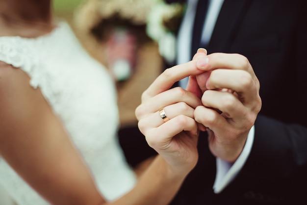 Closeup nouveaux mariés montrent leurs alliances en dansant